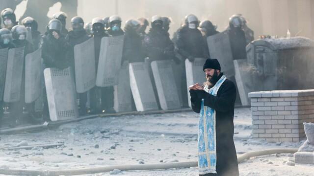 TOP 12 FOTOGRAFII din 2014. Un preot ortodox se roaga in mijlocul protestelor din Kiev
