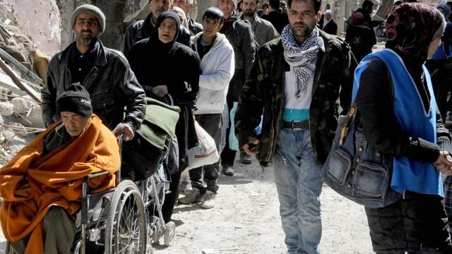 Poza care arata dimensiunea crizei umanitare din Siria. Coada nesfarsita pentru mancare intr-o tabara de refugiati din Damasc - Imaginea 3