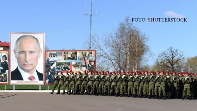 militari rusi defiland prin fata portretului lui Vladimir Putin