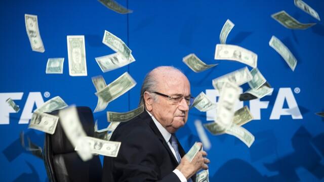 A plouat cu bani peste Sepp Blatter in timpul unei conferinte de presa. Farsa unui comediant britanic l-a scos din sarite