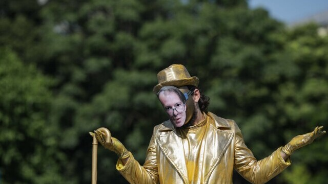 O statuie vivantă cu Florin Cîțu, dezvelită în Piața Victoriei, în cadrul unui protest Greenpeace. GALERIE FOTO - Imaginea 2