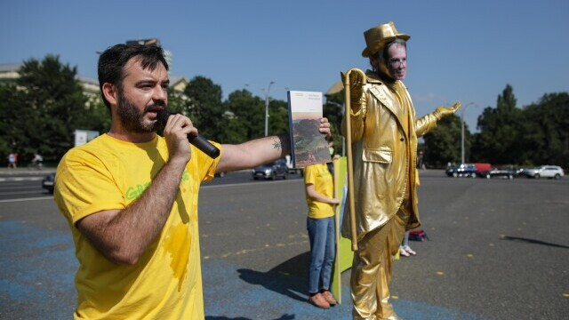 O statuie vivantă cu Florin Cîțu, dezvelită în Piața Victoriei, în cadrul unui protest Greenpeace. GALERIE FOTO - Imaginea 3