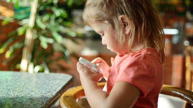copil care se joaca pe telefon