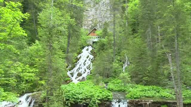 Cascada din România care curge printr-o casă. Se spune că apa ar avea puteri magice