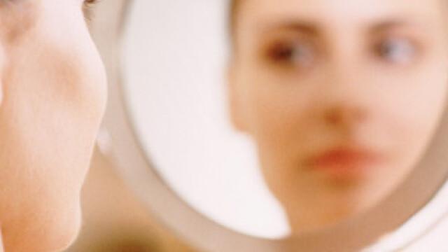 fata se uita in oglinda