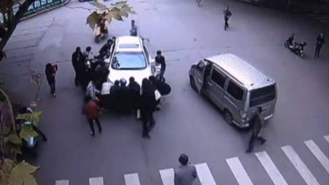 CAMERA DE SUPRAVEGHERE: O femeie este salvata de sub rotile unei masini de trecatori. Momentul in care ridica masina. VIDEO