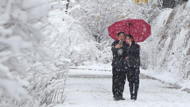 Un cuplu face o poză într-un parc din China, după o ninsoare