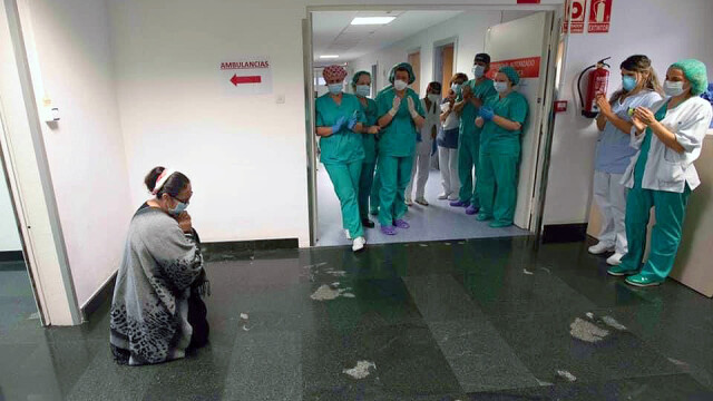 Fotografia anului în Navarra: O româncă îngenuncheată în fața medicilor, care i-au salvat fiul de Covid