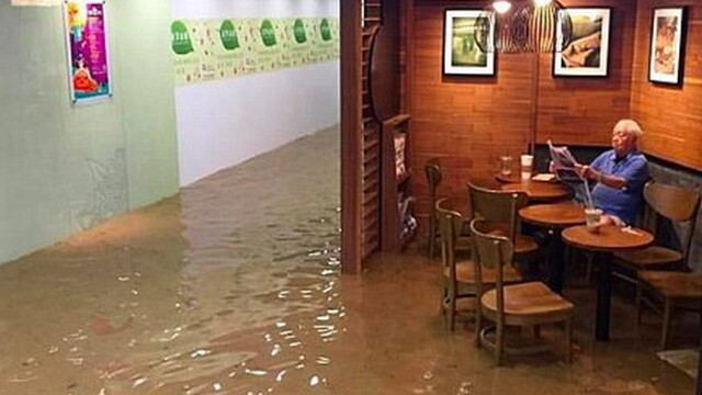 Un barbat citeste ziarul linistit intr-o cafenea inundata din Hong Kong. Povestea din spatele imaginii devenita viral