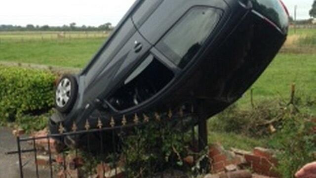 O masina a ramas in pozitie verticala in urma unui accident, dupa ce soferita a trecut cu roata peste o groapa. FOTO - Imaginea 1
