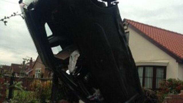 O masina a ramas in pozitie verticala in urma unui accident, dupa ce soferita a trecut cu roata peste o groapa. FOTO - Imaginea 2