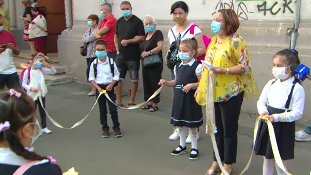 Tabloul începutului de an școlar, în vreme de pandemie. Copiii cu mască la gură, duși cu sfoara în clasă - Imaginea 2