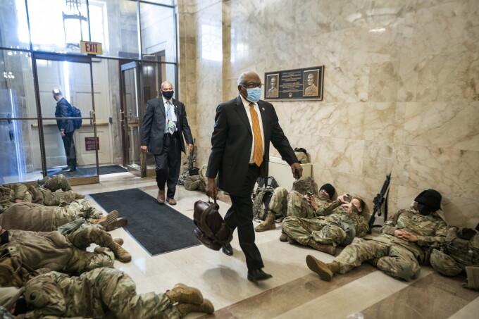 Membri ai Congresului trec printre soldaţii ce păzesc Capitoliul