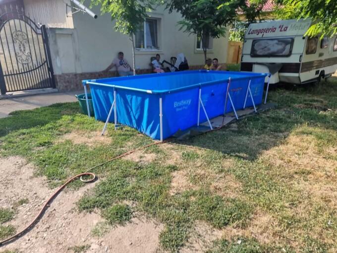 O familie din Timiș și-a făcut piscină în fața casei cu apă adusă de la 50 de metri cu furtunul, de la fântâna publică