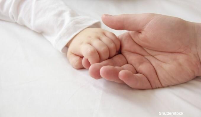 Bebelus care o tine de mana pe mama