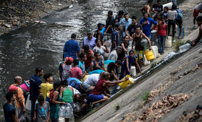 Venezuelenii adună apă dintr-un canal. Pana masivă de curent se prelungește