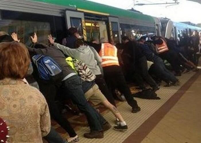 Clipul zilei: Zeci de pasageri au impins vagonul unui tren pentru a ajuta un barbat care cazuse! VIDEO
