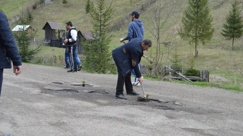 """Flori puse de localnici în gropile unui drum, în semn de protest: """"A băgat țara în noroi"""""""