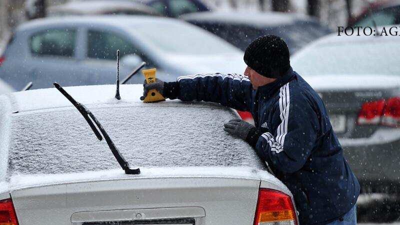 barbat care isi curata masina de zapada in Bucuresti