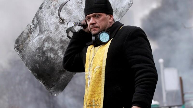 Un preot ortodox tine in mana crucea si un scut, in timpul confruntarilor dintre protestatari si fortele guvernamentale.