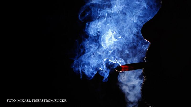 fumator in intuneric cu mult fum de tigara