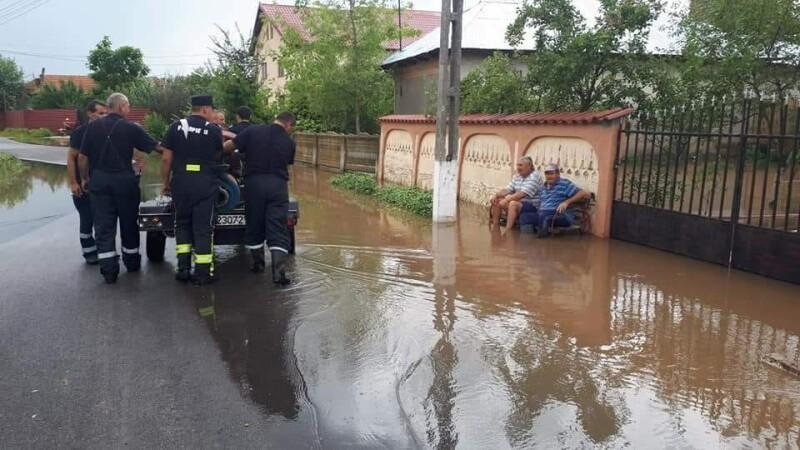 Imaginea zilei, în Teleorman. Pompierii scot apa din curte, localnicii se uită la ei de pe bancă