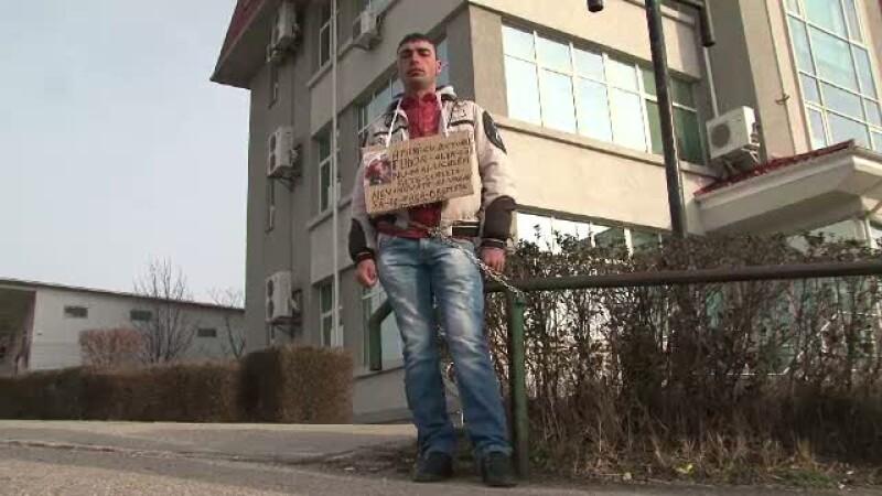 protest, barbat legat cu lant de un gard