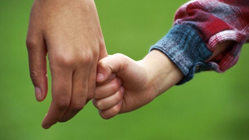 Copil tine de mana