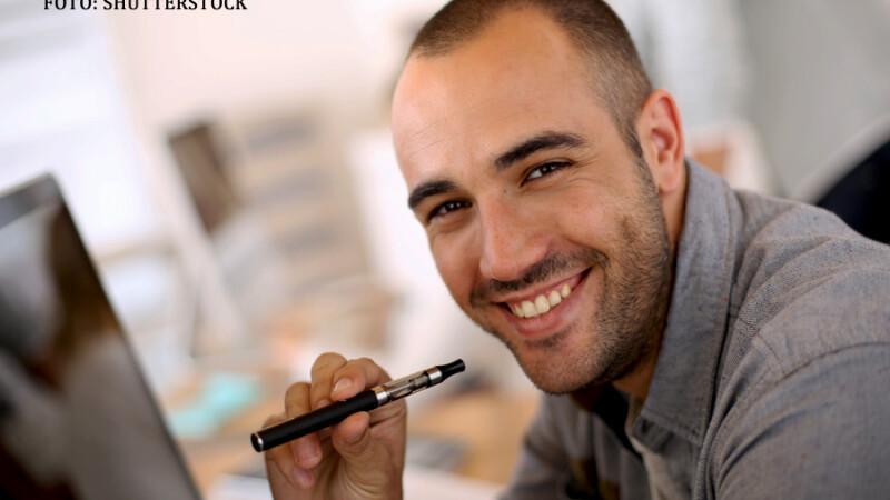 barbat care fumeaza o tigara electronica in fata calculatorului