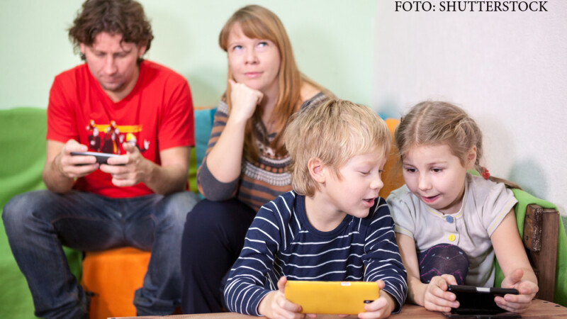 familie care se joaca pe telefoane si tablete