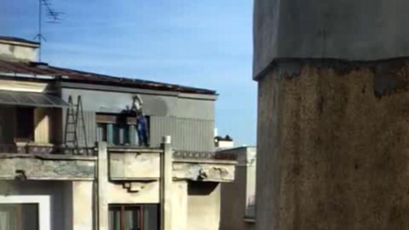 muncitor suit pe balcon