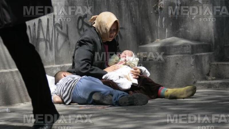 Mama cu copiii, cersind in Piata Universitatii