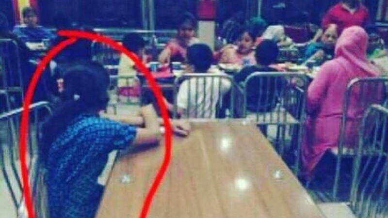 O familie bogata din Indonezia ia masa la un restaurant in timp ce servitoarea se uita la ei cum manaca de la masa alaturata