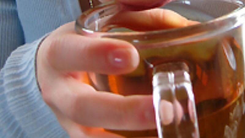 Copil care bea dintr-o halba de bere