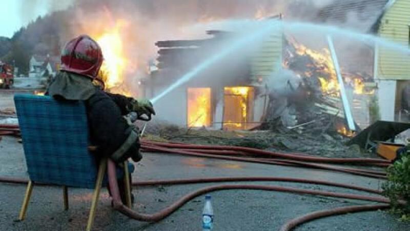 Pompier care stinge focul stand pe scaun