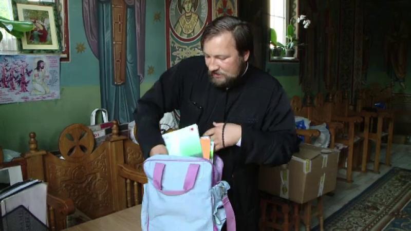 Un preot a cumparat haine si rechizite pentru elevii saraci cu banii din cutia milei. Rasplata pe care o doreste: notele bune