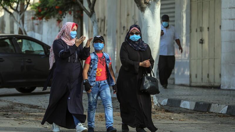 Palestinienii poartă mască de protecție pe stradă. Fâșia Gaza este în carantină din 25 august din cauza Covid-19