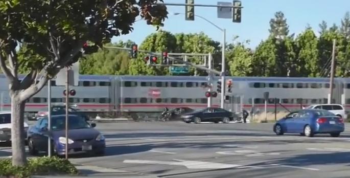 Un politist a salvat in ultima clipa un barbat blocat cu masina pe calea ferata. Soferul a fost tarat inainte sa vina trenul