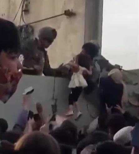 Imagini virale. O fetiţă afgană ridicată din mulţime şi preluată de un soldat peste un zid a devenit simbolul acestor zile