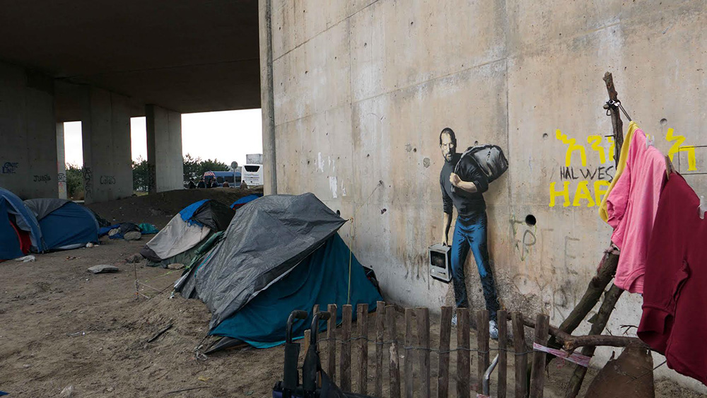 Graffiti-ul realizat peste noapte de Bansky in tabara de refugiati din Calais. Mesajul transmis de artist
