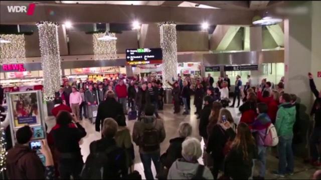Flashmob cu colinde pe aeroportul din Koln. Reprezentatia, demna de o scena de opera