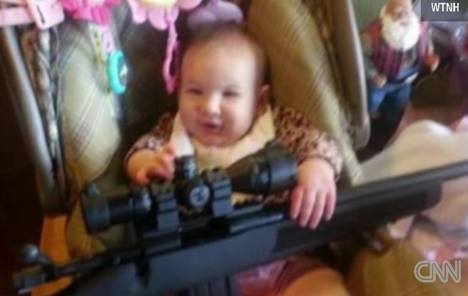 O imagine care a starnit controverse. Un bebelus a fost fotografiat de parinti cu o pusca in brate
