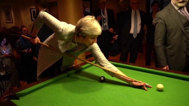 Momentul bizar în care Theresa May e învățată de premierul italian să joace biliard