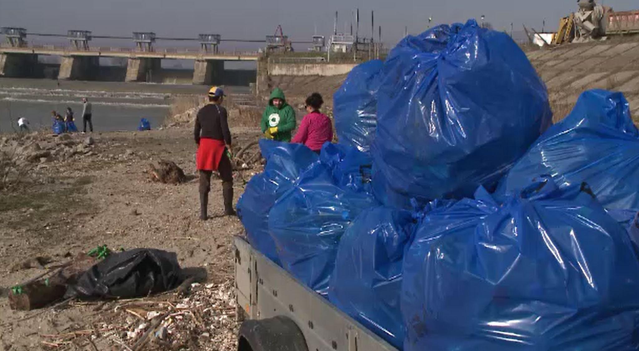 Gunoaiele din zona barajului de la Ișalnița, strânse de voluntari străini.