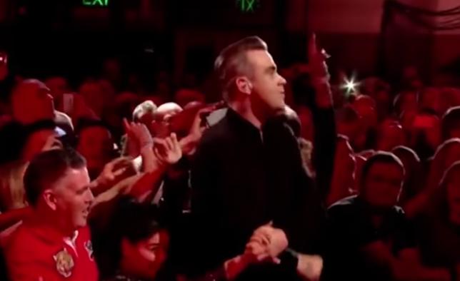 Robbie Williams, filmat in timp ce isi curata mainile cu gel antibacterian dupa ce a dat mana cu mai multi fani. VIDEO