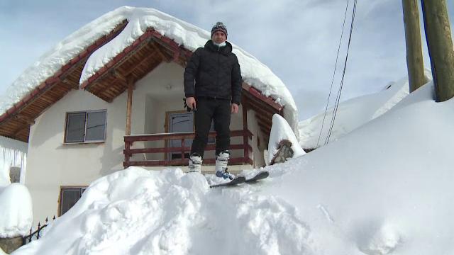 """Cabanele din Rânca, """"înghițite"""" de nămeți de câțiva metri înălțime. Oamenii ies din case pe schiuri"""