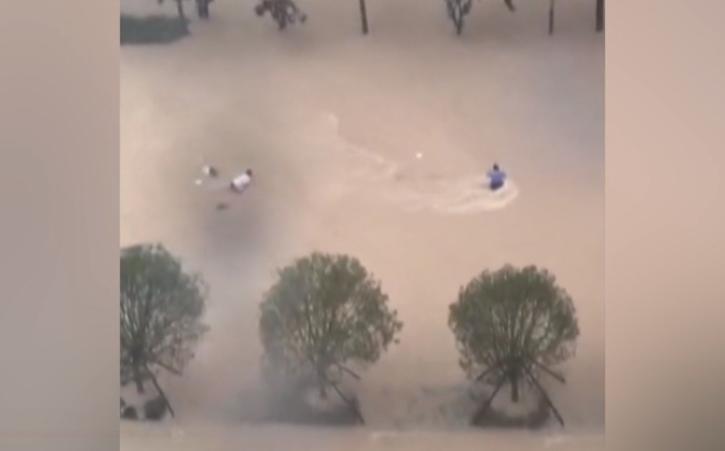 Momentul în care o femeie este luată pe sus de ape, pe o stradă din China. VIDEO