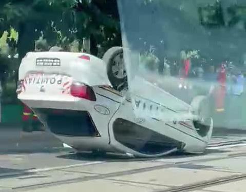 O mașină de poliție în care se aflau și doi reținuti s-a răsturnat, în Capitală. VIDEO