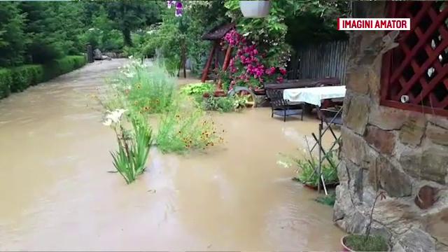 """Blocați în case de apa de un metru ce a inundat strada: """"Primarul să facă diguri, nu ziua comunei"""""""