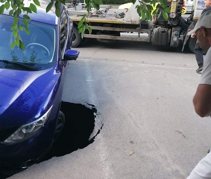 O mașină a rămas suspendată într-o groapă apărută în asfalt, în Craiova. VIDEO